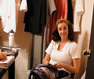 Just part of the job. Actor Bobbi Kravis repairs a costume in her dressing room backstage.