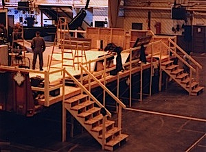 Instant theater: 2 flatbed trailers covered with a plywood stage floor inside a hanger